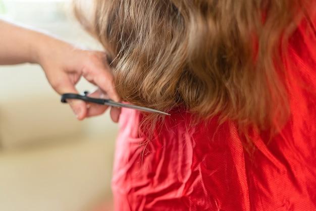 Zamknij się w rękach fryzjera cięcia brązowe włosy w domu.