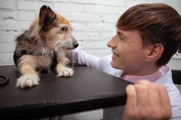 Zamknij się wesoły weterynarz uśmiechając się do uroczego psa schroniska rasy mieszanej leżącego na stole do badań lekarskich