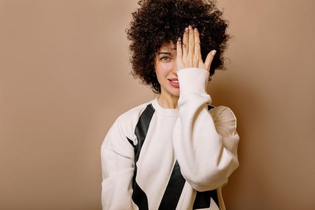 Zamknij się wewnątrz portretu uroczej ukochanej dziewczyny z fryzurą afro, patrząc z przodu z uśmiechem i zakrywającą twarz jedną ręką na beżowej ścianie