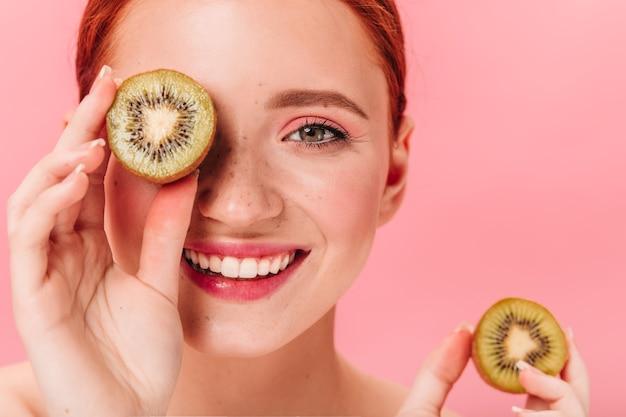 Zamknij się widok błogiej kobiety z kiwi. studio strzałów uśmiechnięta modelka z owocami tropikalnymi.