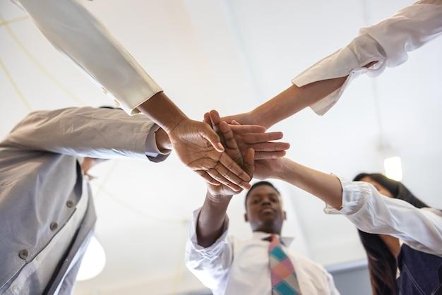 Zamknij się widok młodych ludzi biznesu, składając ręce. stos rąk. koncepcja jedności i pracy zespołowej. studenci wieloetnicznych szkół wyższych układają ręce