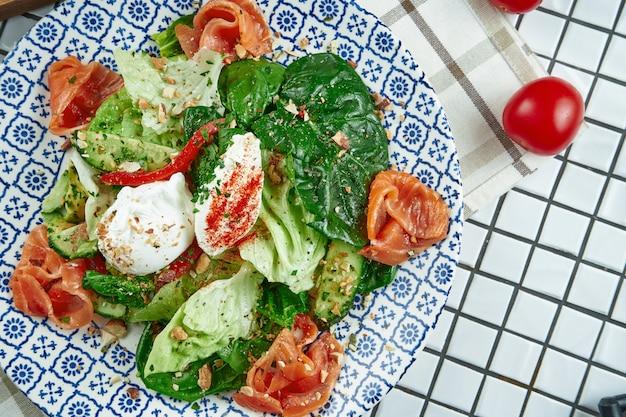 Zamknij się widok na apetyczną sałatkę z łososiem, szpinakiem, jajkiem w koszulce i ricottą w pięknym niebieskim talerzu ceramicznym na białej powierzchni. smaczne jedzenie. leżał płasko