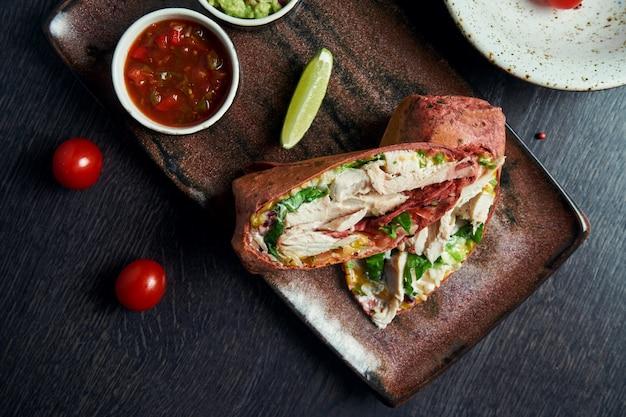 Zamknij się widok na burrito z kurczakiem, ryżem, pomidorami, kukurydzą i papryką w brązowym pita na brązowym talerzu z salsą pomidorową i guacamole. wegetariańska shawarma roll