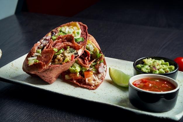 Zamknij się widok na burrito z salami chorizo, ryżem, pomidorami, kukurydzą i papryką w brązowym pita na brązowym talerzu z salsą pomidorową i guacamole. wegetariańska shawarma roll
