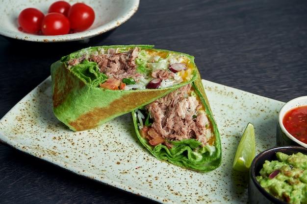 Zamknij się widok na burrito z wołowiną, ryżem, pomidorami, kukurydzą i papryką w zielonej picie na brązowym talerzu z salsą pomidorową i guacamole. wegetariańska shawarma roll