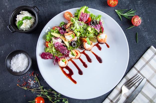 Zamknij się widok na pyszne sałatki z łososiem, serem śmietankowym, awokado i brązowym sosem sojowym na ciemnym tle. smaczna, zdrowa sałatka na lunch na ciemnym tle. owoce morza. płaskie jedzenie