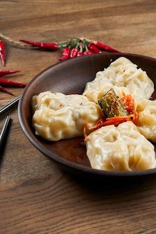 Zamknij się widok na smaczne pierożki na parze nadziewane różnymi składnikami w ceramicznej misce. tradycyjne danie kuchni koreańskiej - mandu lub manti