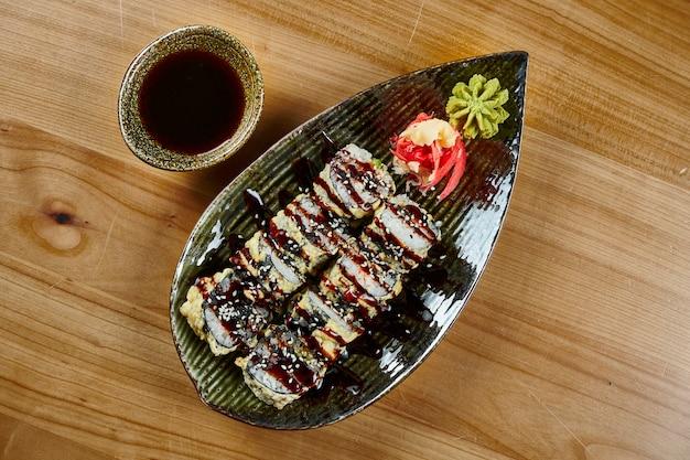 Zamknij się widok na smaczne smażone sushi z krabem, kawiorem tobiko na czarnym talerzu z sosem sojowym