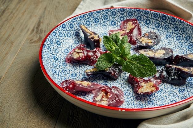 Zamknij się widok na smaczne, tradycyjne gruzińskie jedzenie churchkhela w kształcie świeczki cukierki wykonane z soku winogronowego, orzechów i mąki w niebieskim talerzu na drewnianej powierzchni