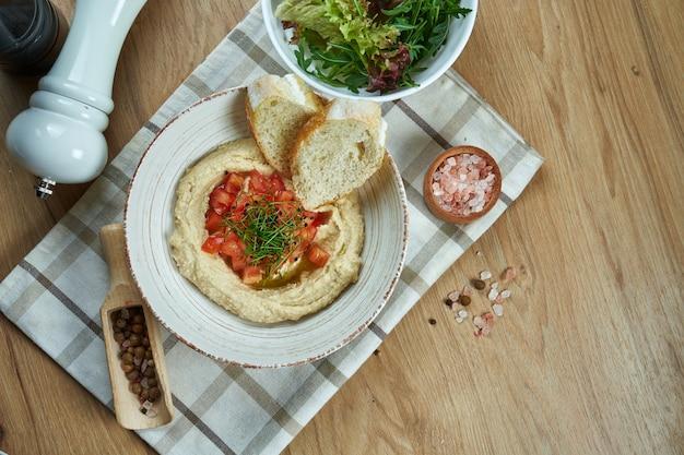 Zamknij się widok na smaczny talerz arabskiego, izraelskiego lub libańskiego wegetariańskiego hummusu z ciecierzycy z pita i warzywami tradycyjna kuchnia orientalna zakąska.
