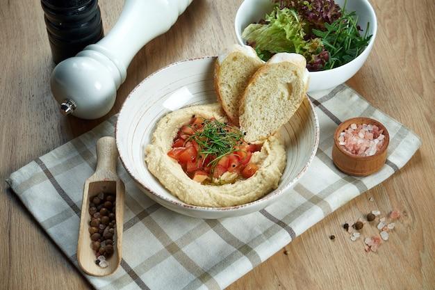 Zamknij się widok na smaczny talerz arabskiego wegetariańskiego hummusu z ciecierzycy z pita i warzywami tradycyjna kuchnia orientalna zakąska.
