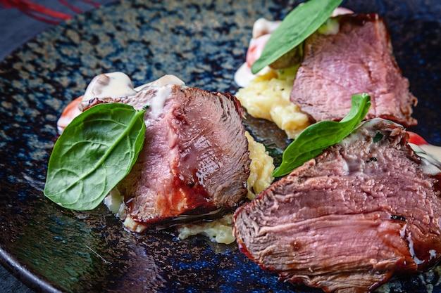 Zamknij się widok na soczysty stek wołowy średnio pieczony w plastrach z krwią podany na ciemnym talerzu z pomidorem i puree ziemniaczanym. jedzenie mięsa amerykańskie jedzenie. skopiuj miejsce na projekt
