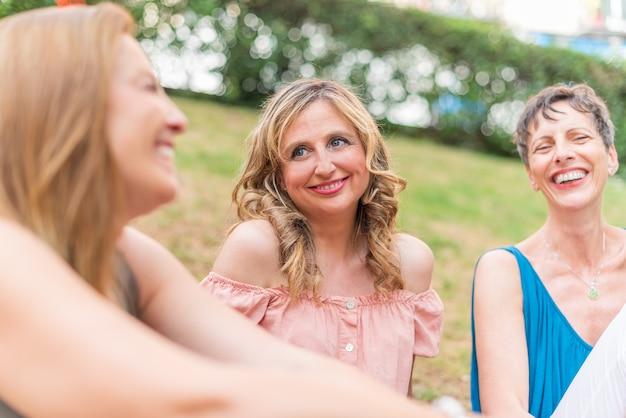 Zamknij się widok trzech dorosłych kobiet siedzących w parku śmiejąc się. piękne dojrzałe kobiety bawią się razem w parku.