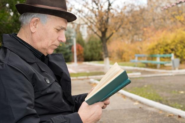 Zamknij się widok z boku portret starszego pana w płaszczu i kapeluszu, czytając jego książkę na zewnątrz