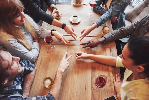 Zamknij się widok z góry młodych ludzi, łącząc ręce. przyjaciele robią kształt gwiazdy palcami pokazującymi jedność i pracę zespołową