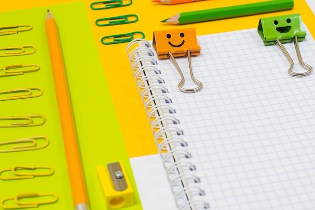 Zamknij się widok z góry zdjęcie jasnych kolorowych przyborów szkolnych. zestaw spiralnego notatnika, ołówków, spinaczy i temperówki na pomarańczowym i zielonym tle