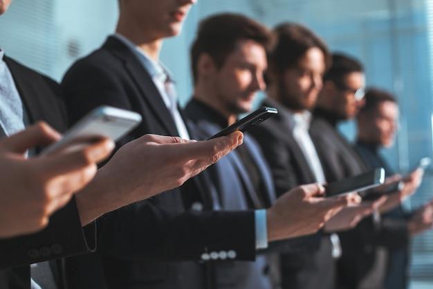 Zamknij się. wizerunek grupy młodych ludzi biznesu ze smartfonami. ludzie i technologia