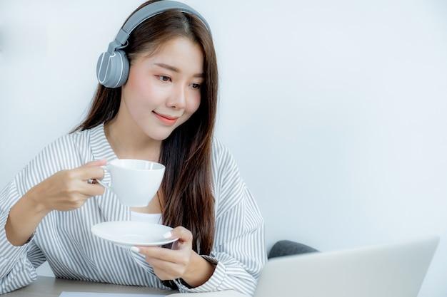 Zamknij się z azji portret kobiety ze słuchawkami, trzymając filiżankę kawy i patrząc na laptopa.