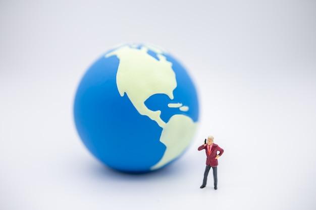 Zamknij się z biznesmenem miniaturową postać stoi i zadzwoń do telefonu z mini świata piłki na białym tle