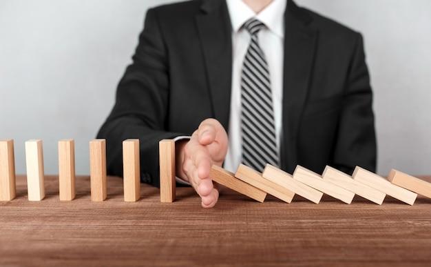 Zamknij się z biznesmenem zatrzymując domino przed upadkiem na biurku.