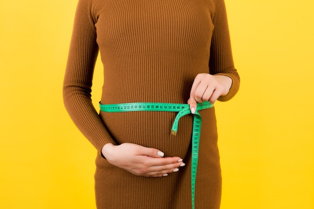 Zamknij Się Z Centymetrem Na Brzuchu Kobiety W Ciąży W Brązowej Sukience Na żółtym Tle. Pomiar Rosnącego Brzucha. Skopiuj Miejsce. Premium Zdjęcia
