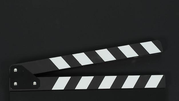 Zamknij się z czarnej płyty clapper lub łupków filmowych na czarnym tle.
