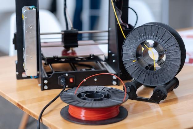 Zamknij się z czerwonym filamentem drukarki 3d leżącym na stole, gdy jest gotowy do użycia