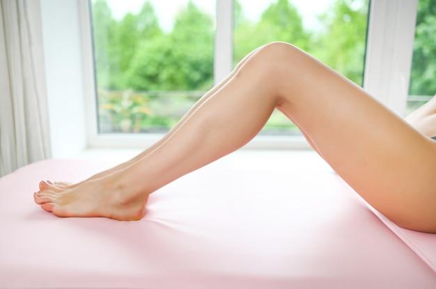 Zamknij się z długimi garbowanymi kobiecymi nogami z idealnie gładką miękką skórą i pedicure