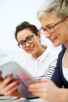 Zamknij się z dwóch uroczych stylowych kobiet w średnim wieku biznesu i czytania produktywnych materiałów, siedząc w biurze jeden obok drugiego.