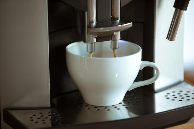 Zamknij się z ekspresu do kawy wlewając cappuccino, espresso, americano w białej filiżance w domu lub kawiarni. smaczny i aromatyczny gorący napój. jedzenie, odżywianie, najpopularniejszy napój na śniadanie i przerwę w pracy.