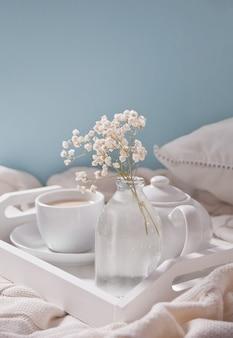 Zamknij się z filiżanką herbaty, mleka, czajnik i bukiet białych kwiatów na białej tacy.