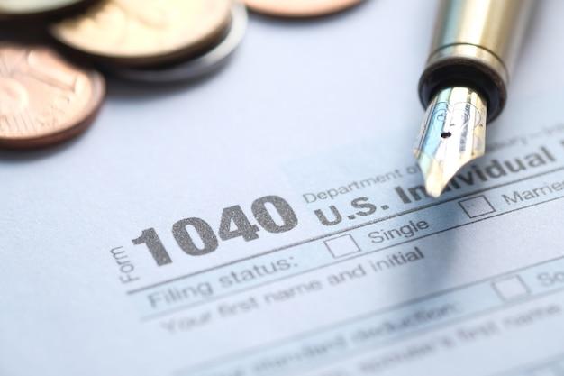 Zamknij się z formularza zwrotu podatku i długopis w tabeli.