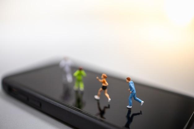Zamknij się z grupy biegacz miniaturowy rysunek działa na ekranie inteligentnego telefonu komórkowego.