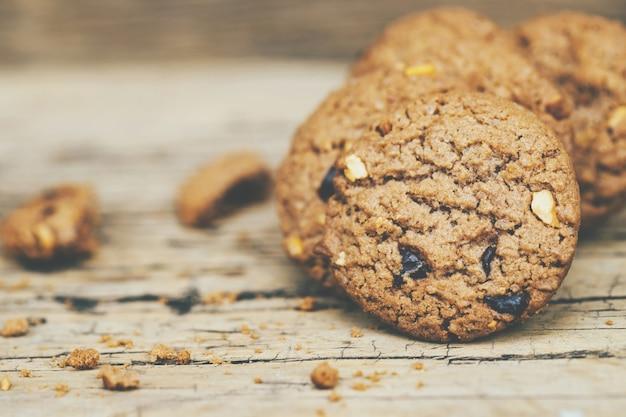 Zamknij się z grupy ciasteczka czekoladowe wiele ułożone na ciemnym starym rustykalnym drewnianym stole deski