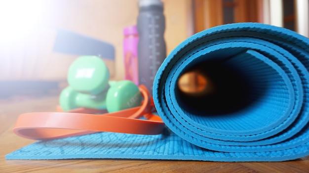 Zamknij się z jogi, mata podłogowa fitness w domu w rolce. rekwizyty i akcesoria do jogi, mata turkusowa. koncepcja zdrowego stylu życia