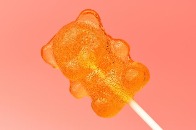 Zamknij się z karmelem lollipop na patyku w kształcie niedźwiedzia na różowej powierzchni