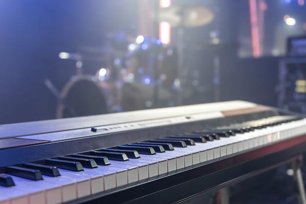 Zamknij się z klawiszami muzycznymi w pomieszczeniu z pięknym oświetleniem.