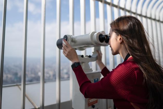 Zamknij się z kobietą patrząc na miasto przez teleskop (lornetka) na szczycie budynku.