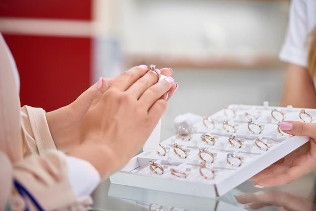 Zamknij się z kobietą przymierzającą pierścionek zaręczynowy w sklepie jubilerskim