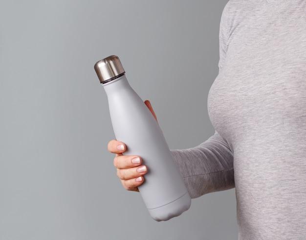 Zamknij się z kobieta w szarej koszulce, trzymając szarą butelkę
