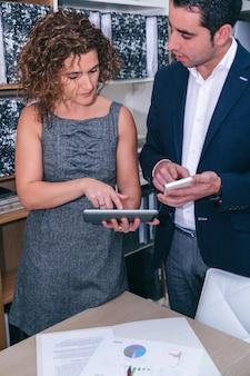 Zamknij się z kolegami patrzącymi na dokument w elektronicznym tablecie na spotkaniu biznesowym