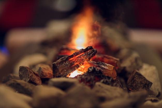 Zamknij się z kominkiem elektrycznym z pomarańczowym i żółtym płomieniem ognia.