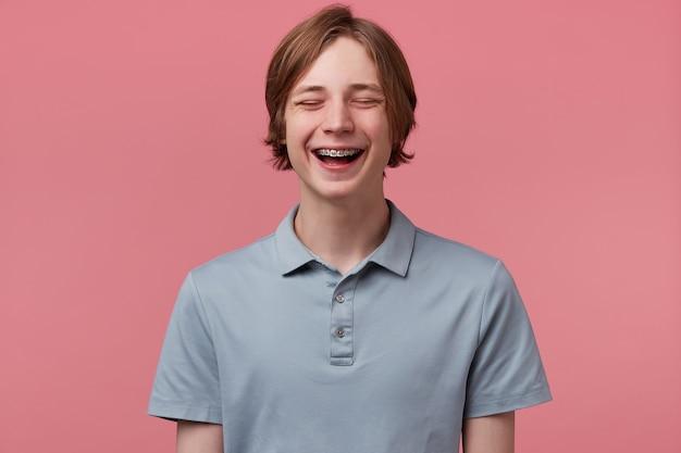 Zamknij się z ładnym niebieskookim, starannie uczesanym młodym facetem z szelkami na zębach, radośnie się śmiejąc, zamknął oczy zabawy, nosi koszulkę polo, wygląda na szczęśliwą na różowym tle