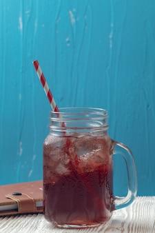 Zamknij się z lodem sok z granatów w szkle na stole