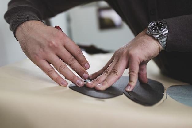 Zamknij się z męskiego szewca pracy z tekstyliów skórzanych w jego warsztacie.