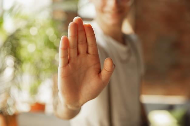 Zamknij się z męskiej dłoni pokazując znak zatrzymania, odrzucenia. koncepcja edukacji, freelance, biznesu i komunikacji. kaukaski model mężczyzna w pomieszczeniu, zapraszając, pokazując. miejsce na reklamę.