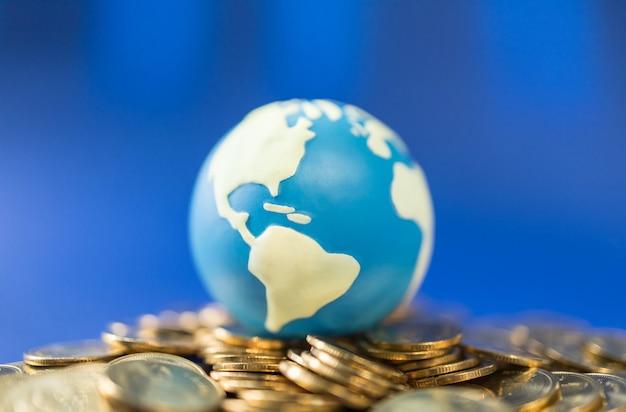 Zamknij się z mini kuli świata na stosie złotych monet