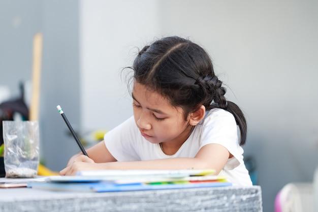 Zamknij się z młodą dziewczyną, koncentrując się na jej pracy domowej