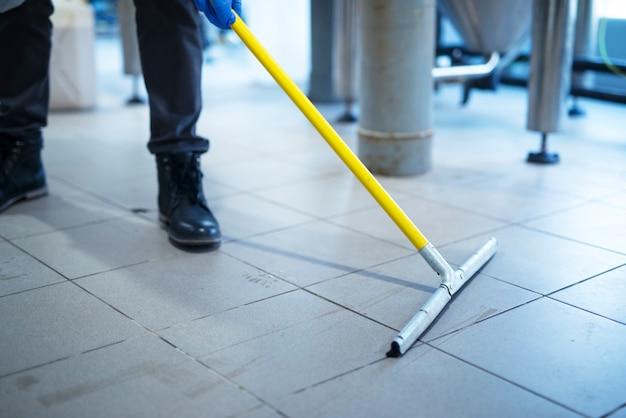 Zamknij się z mopem do czyszczenia podłogi zakładu przemysłowego