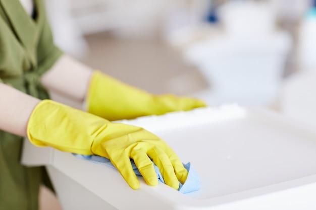Zamknij się z nierozpoznawalną kobietą w żółtych gumowych rękawiczkach podczas czyszczenia plastikowych pojemników w domu